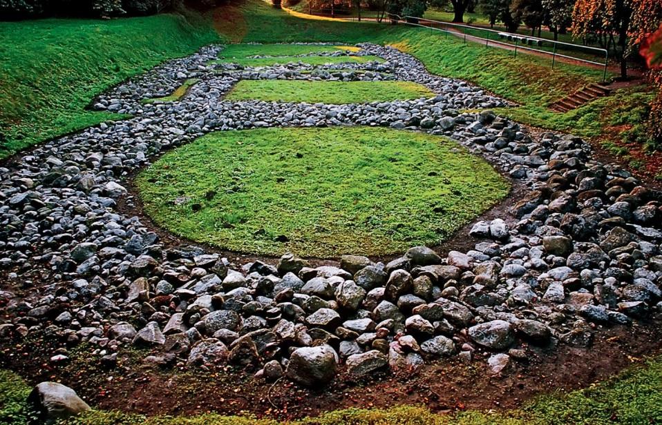 Fundamenty pałacu książęcego w Grodzie w Gieczu, na tle trawy widoczny zarys palatium, w którym dominują kamienie